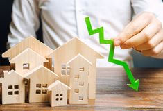Analyst holds down arrow near the wooden houses. Concept of falling real estate market. Low prices and cost of housing. Reduced. Mortgage rates and housing stock photo