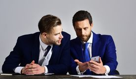 Analyst holds smartphone and explains new business plan. Businessman consults with financial analyst having serious face. Managers in formal suits discuss stock photos