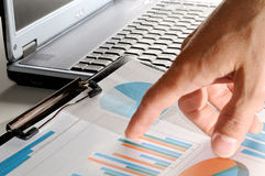Analyst pointing values on a graph Stock Photos
