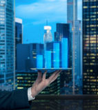 Analyst's hand is holding a gadget with bar chart projection of the expected revenue of the company. Analyst's hand is holding a gadget with bar chart stock images