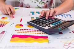 Analyst`s hands with business graphs, pen. And calculator royalty free stock photography