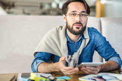 Analyst at work. Brainstorming businessman sitting by his workplace during work stock photography