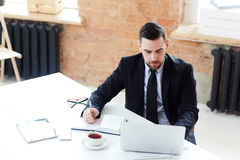 Analyst at work. Serious boss having online communication in office royalty free stock image