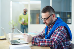 Analyst at work. Young manager in casualwear reading papers in office royalty free stock photography