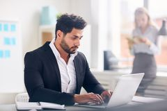 Analyst working in office. Serious financier sitting by desk in front of laptop and analyzing online statistics stock photo