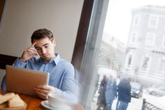 Analyst working. Pensive young man looking at online data in touchpad stock photo