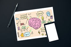 Analytical and creative thinking concept. Dark desktop with creative brain sketch, blank smartphone, pen and paper clips. Analytical and creative thinking Royalty Free Stock Images