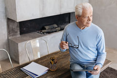 Analytical intelligent gentleman reading morning news. Keeping up with the world. Nice jolly mature man sitting on a table in his home office and using his Stock Photography