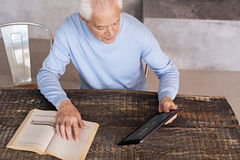 Analytical intelligent man choosing a better device. Comparing possibilities. Inventive persistent elderly gentleman sitting at the table and making a decision Stock Photo