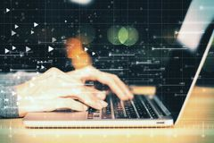 Analytics and economy concept. Side view of hands using laptop with glowing forex chart hologram on blurry background. Double exposure stock photos