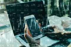 Analytics and trade concept. Side view of hands using laptop and smartphone with glowing forex chart hologram on blurry background. Double exposure stock images