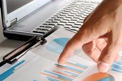 Analytiker som pekar ‹för †för värdepå en graf Arkivfoton