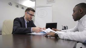 Analytique financier masculin discute des taux de bitcoin avec son patron africain dans le bureau banque de vidéos