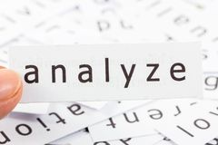 Analyze closeup. Analyze word on paper picked by finger to see close stock photo