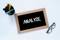 Analyze - isolated word in top view of blackboard. Business analyze to get goal. Glasses, marker and pen case stock photo