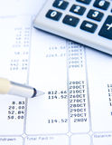 Analyzing a bank statement. A pen and calculator on top of a bank statement with the pen pointing to a particular item. An abstract image underlining the need Stock Photos