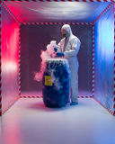 Analyzing bio hazardous waste in containment tent. Person in a protective suit and gas mask working with steaming substances over a blue waste drum marked as bio royalty free stock photography