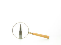 Analyzing a bullet through a magnifying glass Stock Images