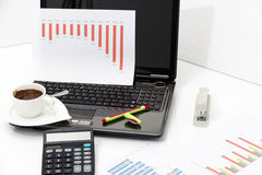 Analyzing business investment charts with calculator and laptop. Photo of the Analyzing business investment charts with calculator and laptop Stock Photo