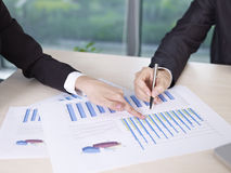 Analyzing business performance. Two business executives analyzing business performance in office Stock Photos