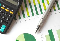 Analyzing a chart. Closeup of a business chart with pen and calculator Royalty Free Stock Photography