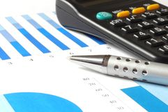 Analyzing a chart. Closeup of a business chart with pen and calculator Royalty Free Stock Photo