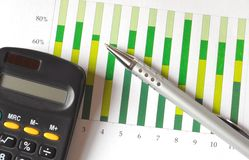 Analyzing a chart. Closeup of a business chart with pen and calculator Royalty Free Stock Photos