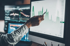 Analyzing data. Close-up of young businessman pointing on the data presented in the chart with pen while working in creative office royalty free stock photos