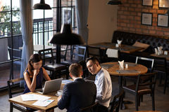 Analyzing earnings. Restaurant owners analyzing earnings at the table Stock Image