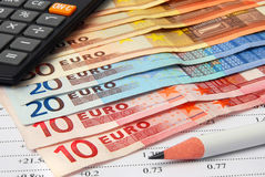 Analyzing financial data. Euro banknotes, pencil and calculator on a sheet of financial data stock photography