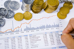 Analyzing financial report with coins around it Stock Image