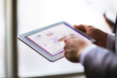 Analyzing financial statistics displayed. Business person analyzing financial statistics displayed on the tablet screen Stock Photo