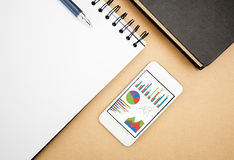 Analyzing graph on smart phone. With notebook on office table Royalty Free Stock Photos