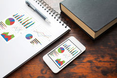 Analyzing graph on smart phone. With notebook on office table Royalty Free Stock Images