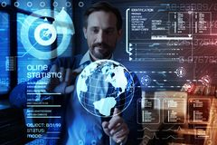 Smart programmer touching virtual planet while working with transparent screen. Analyzing information. Experienced clever calm programmer touching a realistic royalty free stock photo