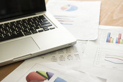 Analyzing investment charts with laptop. Accounting Stock Photography