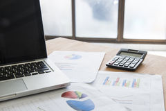 Analyzing investment charts with laptop. Accounting Stock Images
