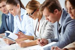 Analyzing progress. Female looking through business papers at briefing among her colleagues stock image