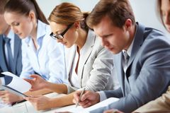 Analyzing progress. Female looking through business papers at briefing among her colleagues royalty free stock photos