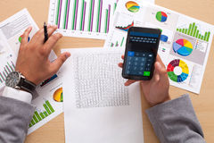 Analyzing statistics with smart phone calculator Stock Photos