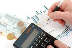 Analyzing stock graph, businessman workplace. With money, coins, pen and calculator Royalty Free Stock Photography