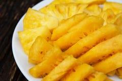 Ananas affettato sul piatto bianco sulla tavola immagini stock libere da diritti