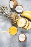 Ananas, banaan en kokosnotencocktail of sap in glas op een concrete achtergrond royalty-vrije stock foto's