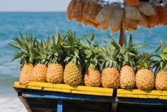 Ananas da vendere sulla spiaggia tropicale Fotografie Stock Libere da Diritti