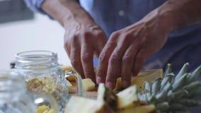 Ananas del taglio delle mani del cuoco unico sul tagliere di legno Uomo che prepara il dessert della frutta video d archivio