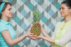 Ananas della tenuta di due bello donne insieme Immagine Stock