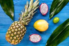 Ananas, dragonfruit et chaux sur la vue supérieure de fond en bois bleu de bureau Photo stock