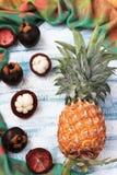 Ananas e mangostano su un fondo blu, vista superiore immagine stock