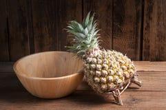 Ananas e vassoio di legno su un fondo di legno della tavola Fotografia Stock Libera da Diritti