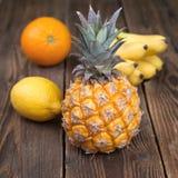 Ananas ed altri frutti tropicali su legno Fotografia Stock Libera da Diritti